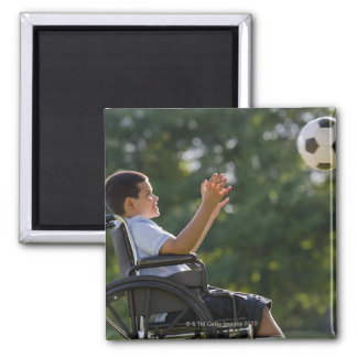 Hispanic boy, 8, in wheelchair with soccer ball magnet