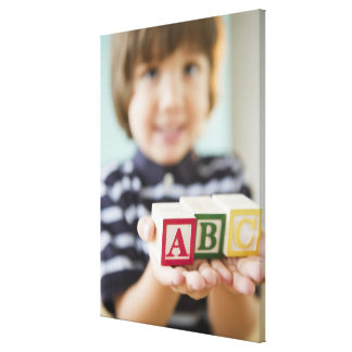 Hispanic boy holding alphabet blocks canvas print