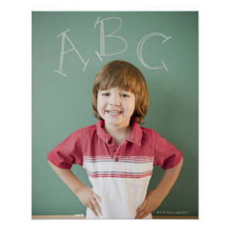 Hispanic boy standing underneath abcs on poster