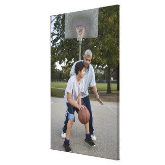 Hispanic father and son playing basketball canvas print