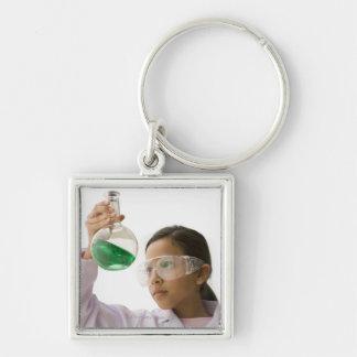 Hispanic girl looking at liquid in beaker key chain