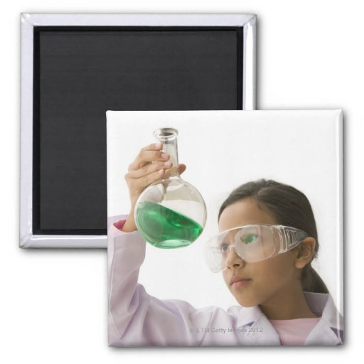 Hispanic girl looking at liquid in beaker magnet