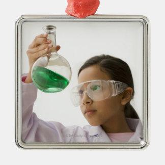 Hispanic girl looking at liquid in beaker metal ornament