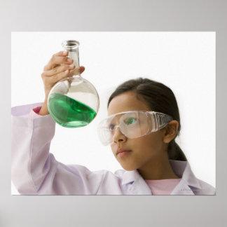 Hispanic girl looking at liquid in beaker poster
