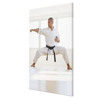 Hispanic male karate black belt in fighting stretched canvas print
