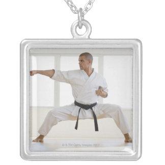 Hispanic male karate black belt in fighting pendant