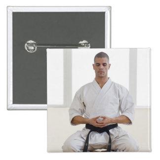 Hispanic male karate black belt meditating button