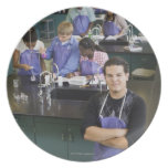 Hispanic student standing in chemistry lab dinner plate