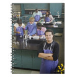 Hispanic student standing in chemistry lab spiral notebook