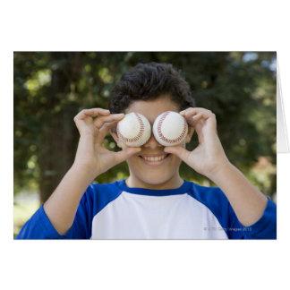 Hispanic teenage boy covering eyes with card