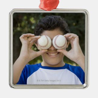 Hispanic teenage boy covering eyes with metal ornament