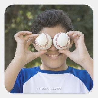 Hispanic teenage boy covering eyes with square sticker