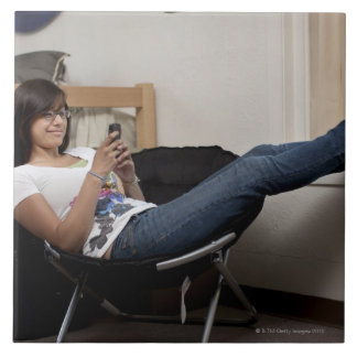 Hispanic woman hanging out in college dorm room large square tile