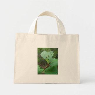Hoja verde con los agujeros bolsas lienzo
