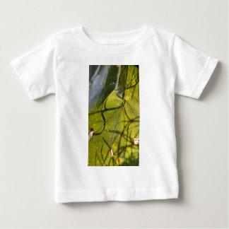 hoja verde con los tendrils del musgo español en playera de bebé