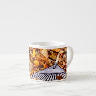 Hojas de la caída con el rastrillo taza espresso
