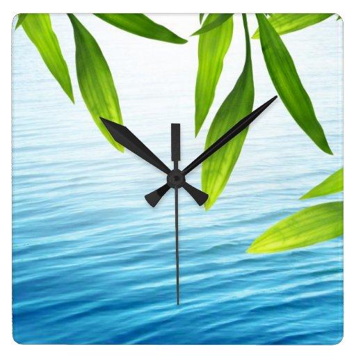 Hojas del bambú y reloj de pared del agua
