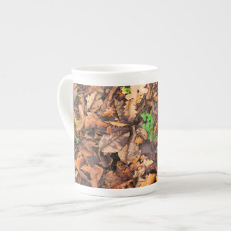 Hojas secas del otoño y tréboles verdes tazas de china