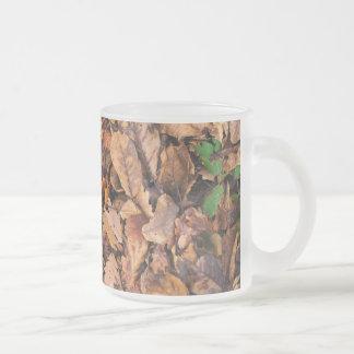Hojas secas del otoño y tréboles verdes tazas