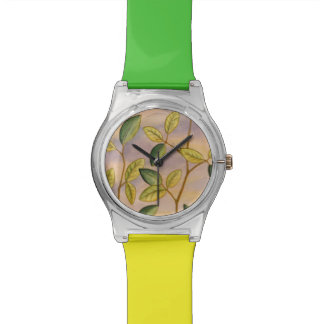 Hojas verdes y amarillas en fondo de la puesta del relojes de mano