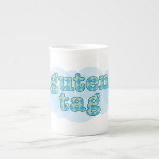 Hola en alemán guten la etiqueta con el modelo del taza de porcelana