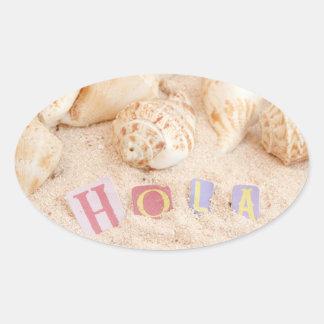 Hola, hello in Spanish on a sandy beach Oval Sticker