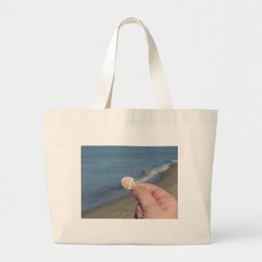 Holding a seashell in the hand large tote bag