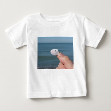 Beach Themed Holding a seashell in the hand with blue sea baby T-Shirt