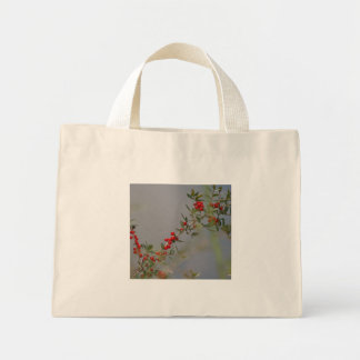 Holly berry stem against grey background tote bags