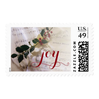 Holly branch on top of sheet music for Christmas Postage
