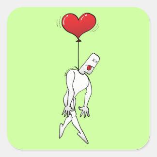 Hombre colgado por un globo del corazón
