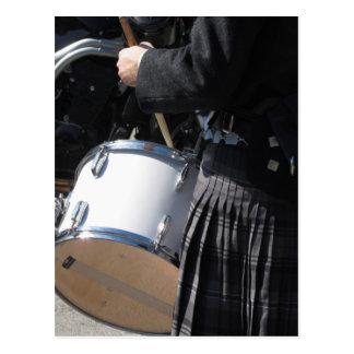 Hombre con la falda escocesa que juega en los postales