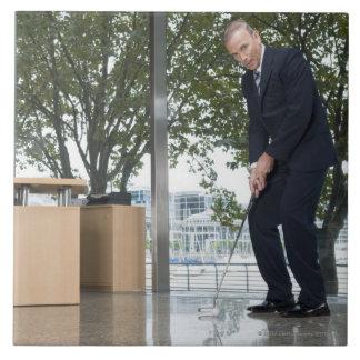 Hombre de negocios que juega a golf en una oficina azulejo cuadrado grande