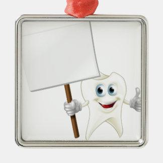 Hombre del diente que lleva a cabo una muestra adorno navideño cuadrado de metal