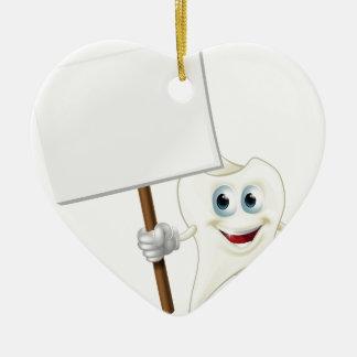 Hombre del diente que lleva a cabo una muestra adorno navideño de cerámica en forma de corazón