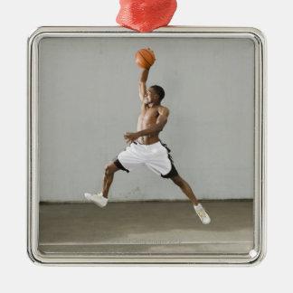 hombre descamisado que salta con un baloncesto adorno navideño cuadrado de metal