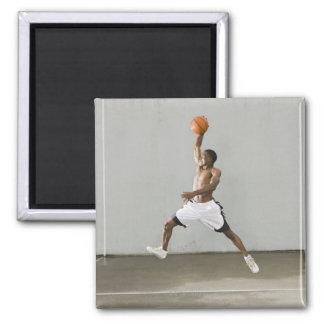 hombre descamisado que salta con un baloncesto imán cuadrado