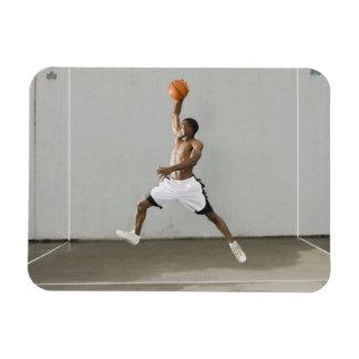 hombre descamisado que salta con un baloncesto imán foto rectangular