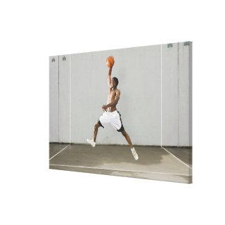 hombre descamisado que salta con un baloncesto impresión en lona estirada