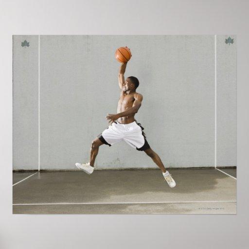 hombre descamisado que salta con un baloncesto posters