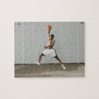 hombre descamisado que salta con un baloncesto rompecabezas con fotos