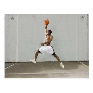 hombre descamisado que salta con un baloncesto tarjeta postal