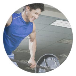 Hombre en el gimnasio, barbell grande de plato de cena