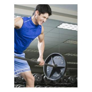 Hombre en el gimnasio, barbell grande de postal