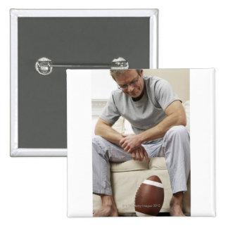 Hombre en el sofá con fútbol pin cuadrado