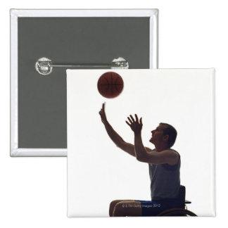 Hombre en la silla de ruedas que juega con balonce pin cuadrada 5 cm