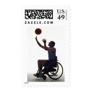 Hombre en la silla de ruedas que juega con sellos