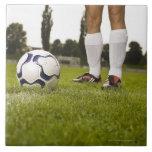 Hombre en la situación uniforme del fútbol con el  azulejo cuadrado grande