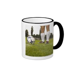 Hombre en la situación uniforme del fútbol con el taza de dos colores
