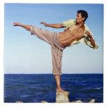 Hombre en los artes marciales que golpean la posic azulejo ceramica